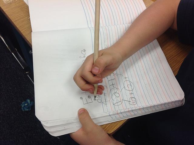 piszące dziecko przy biurku